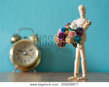 The puppet holds flower a flower in front of gold vintage alarm clock on the wood table. the background is blue and copy space for text