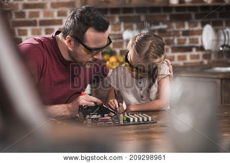 Father Teaching Daughter To Braze