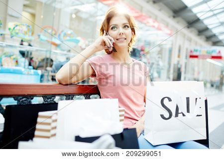 Modern girl with shopping-bags speaking on mobile phone in the mall