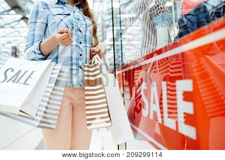 Modern shopper with paperbags standing by shop-window with sale banner