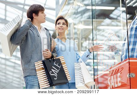 Young sweethearts with paperbags discussing new clothes in display window