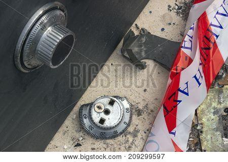Broken combination lock on the safe closeup. Police tape. Concept - burglary robbery crime.