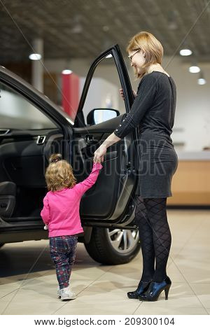 woman with daughter choose car in dealership