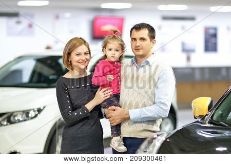 Family buying new car in auto shop