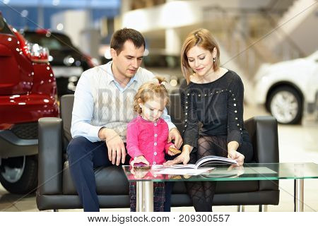 Family buying new car in auto dealership