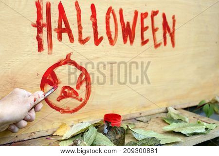 Male hand painting Halloween background on the wooden wall