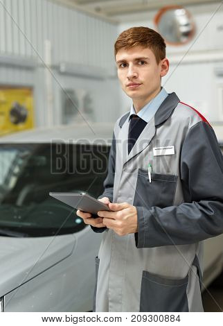 Portrait of a car mechanic in a car workshop, in the background of dealership