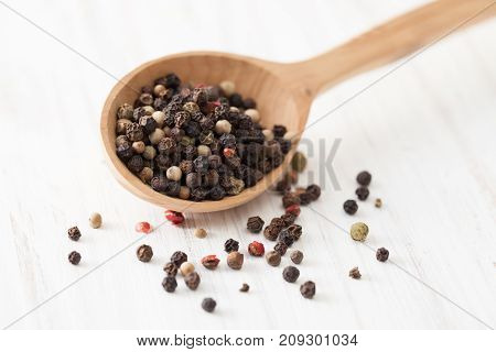 Red, White And Black Pepper In Wooden Spoon On White Wooden Table