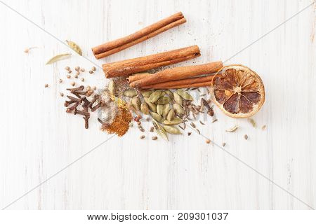Cinnamon, Cloves, Cardamom And A Piece Of Dry Orange On White