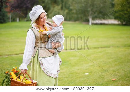 a peasant woman walking with a baby in her arms and with a basket in hand