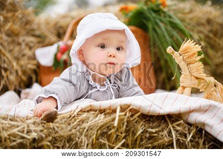 Happy baby in a field with hay rolls at sunset. lies on the hay