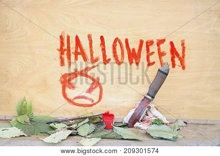 Hallowen painted on the wooden wall paint brush and knife in the foreground