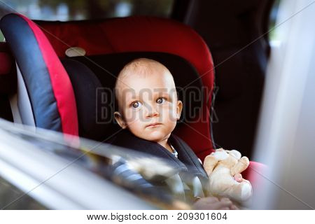 Cute little baby boy sitting in the car seat in the car, looking out. Close up.