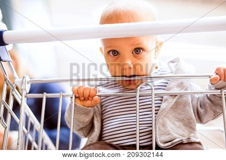 Unrecognizable young mother with her little baby boy at the supermarket, shopping. Close up.