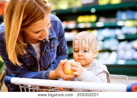 Beautiful young mother with her little baby boy at the supermarket, shopping. Woman giving her son an apple. Close up.