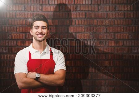 Portrait of confident male owner with arms crossed against full frame shot of wall
