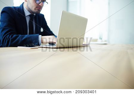 Young employee sitting by workplace and looking through online information
