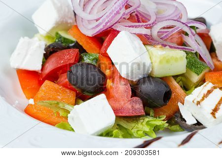 Greek salad with vegetables and red onion on white background