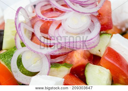 Greek salad with red onion on white background