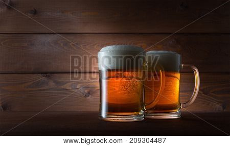 Two glasses golden beer on wooden background