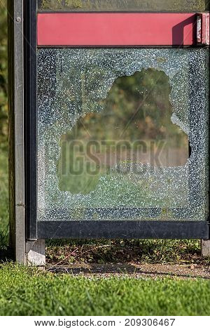 Vandalism with smashed glass on British telephone box. Broken glass caused by anti-social behaviour.