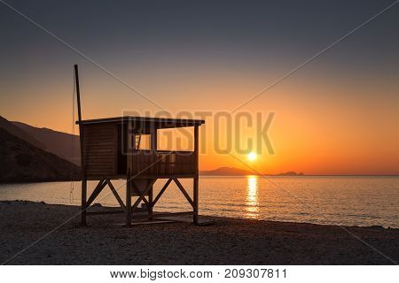Sun Setting Behind Lifeguard Tower On Ostriconi Beach In Corsica