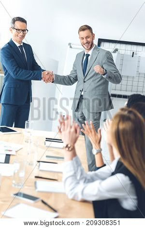 boss shaking hand of manager while colleagues clapping