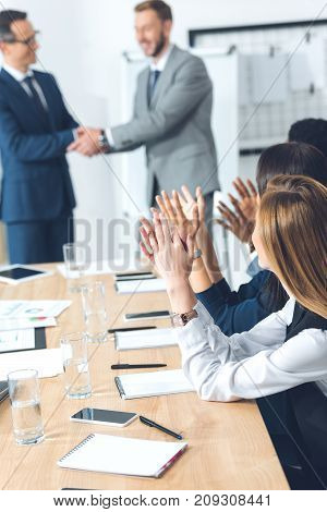 boss shaking hand of manager while colleagues clapping at conference hall