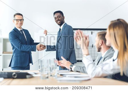 boss shaking hand of african american manager while colleagues clapping