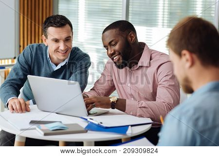 Dictate me. Confident foreigner feeling happiness while being in the office and doing his task with partner