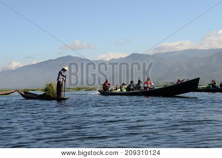 Tourist take photo of Intha woman on Tradition boat transportation at Inle lake floating garden at 18 December 2016 Intha viillageInleMyanmar