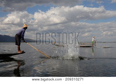 Intha fishermen working on their floating boat by hitting the water to find fish in Inle lake Myanmar on 18 decenber 2016