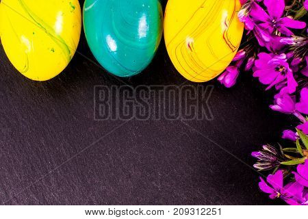close-up of colorful easter eggs and phlox flowers on stone background with copy space. border template, easter greeting and holiday card.