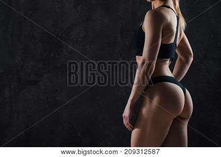 Healthy lifestyle diet and fitness. Beautiful slim woman's body. Perfect slim toned young body of the girl. Fitness or plastic surgery and aesthetic cosmetology. Taut elastic ass. Firm buttocks.