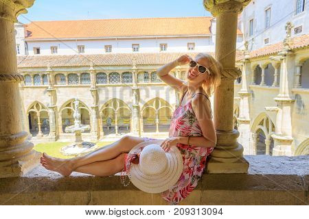 Blonde caucasian woman sitting on colonnade of Santa Cruz Monastery. Silence cloister of blurred background. Female tourist enjoying in university town of Coimbra in Central Portugal, Europe.