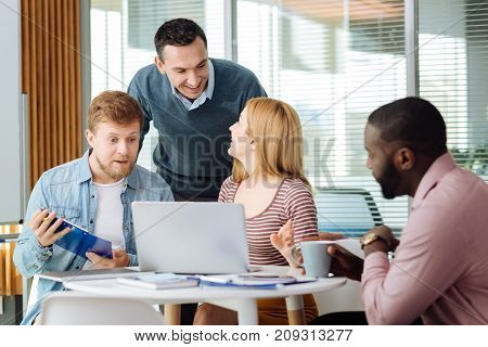 Positive discussion. Handsome brunette male keeping smile on his face and bowing head while talking to his partner