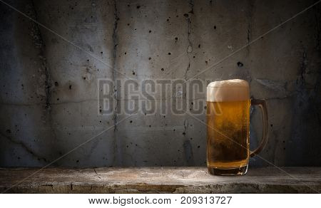 mug of beer on dark background background, hand