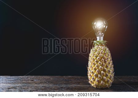 Fresh pine apple with light bulb vitamin and good for health on wooden table with black background.
