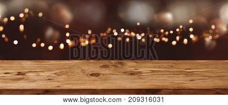 Abstract bokeh background with golden light effects and wooden table for a festive christmas decoration