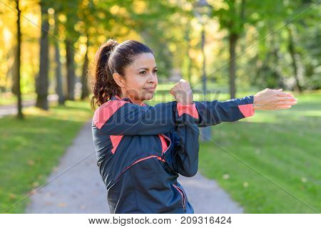 Woman Stretching In Park On Sunny Day