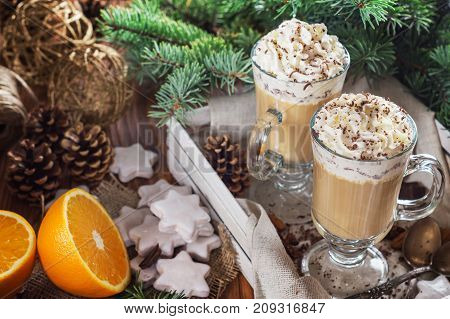 Christmas background with two latte cookies star fir branches cones orange and spices close up. Couple coffee with milk and homemade tasty cookies in tray on wooden background. Top view.