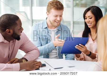 Positive discussion. Handsome international office worker sitting in semi position and leaning elbows on table while using telephone