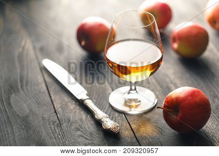Glass of brandy on black wooden background