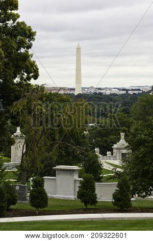 Arlington, Virginia - September 9, 2011 -- Vertical from atop Arlington Cemetery of large tombstones and monuments and the Washington Monument, Washington, DC, in the background, on a bright overcast day in September.