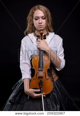 Sad woman with the violin and looking down on black background