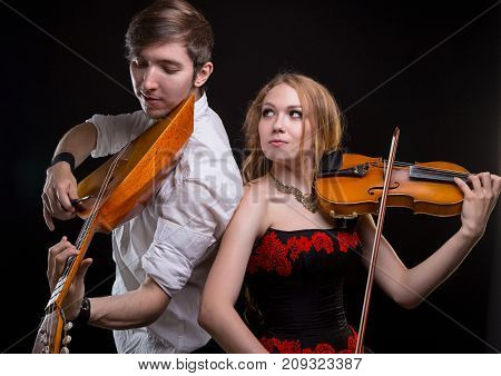 Musical couple with violin and balalaika on black background