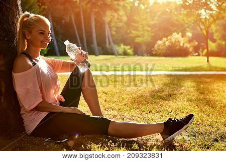 Beautiful young sporty woman sitting at a tree in a park in the sunset and drinking water from a bottle