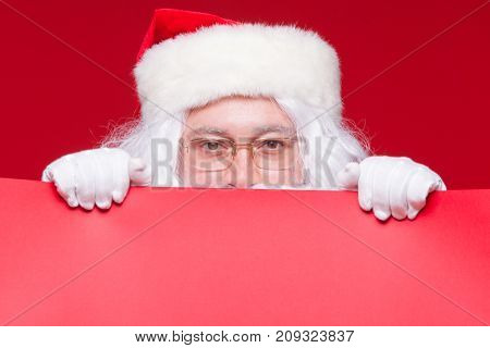 Santa Claus pointing in blank advertisement banner isolated on red background with copy space red leaf.