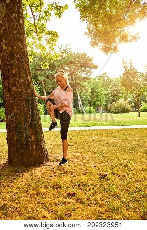 A beautiful young blonde woman leaning to a tree while stretching in a park in the sunset