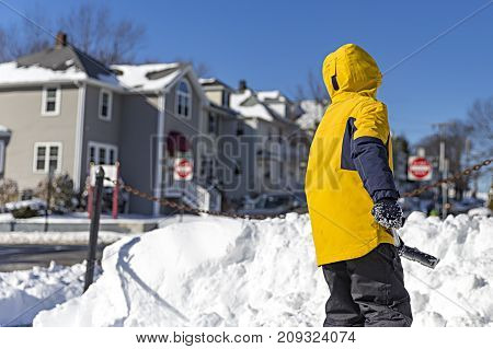 boy shoveling snow. child cleans the snow in the yard. Copy space for your text